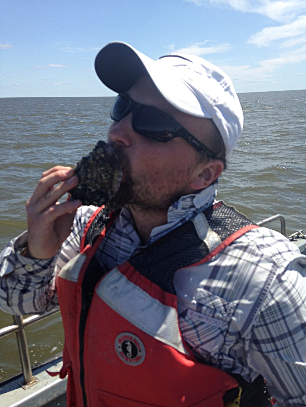 Image of Scott Riley sampling an oyster. Credit: Hollis Jones.