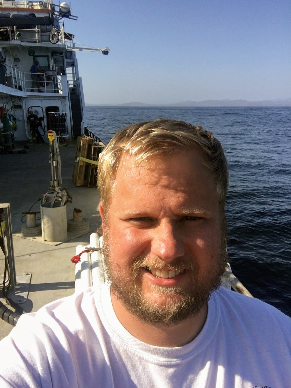 A work selfie on the  R/V Oceanus  as the science crew prepares to cast the CTD behind me. We were just off the coast for this one! - Mike Henson.
