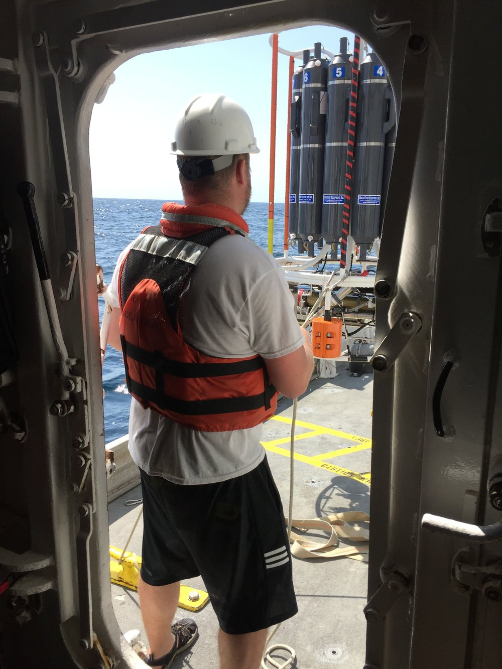 Photo of Mike Henson helping to secure water samples collected onboard the  R/V Oceanus