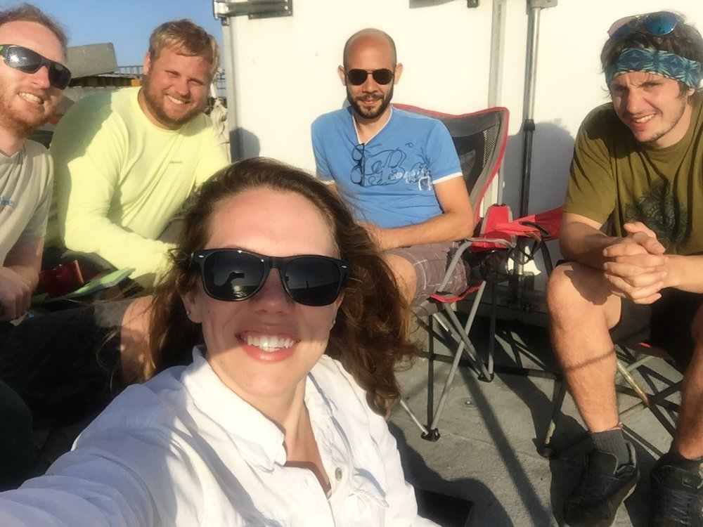 Photo of some of the science crew on the second deck enjoying the sun on a break. Back, Left to Right: Philipp Hach (Student, Max Planck Institute of Marine Microbiology), Mike Henson, Emilio Garcia (Faculty, University of Cádiz), Clemens Schauberger (Student, University of Southern Denmark). Front: Abby Johnson (Student, Georgia Institute of Technology)