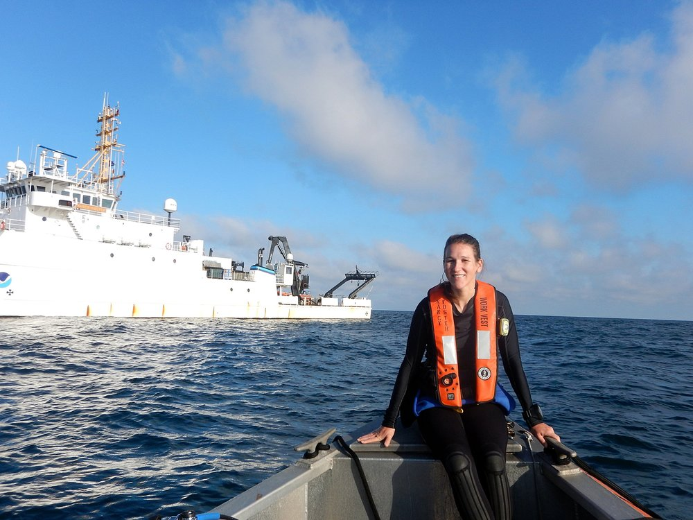 A photo of Alicia on the small vessel with the  R/V Nancy Foster  in the background. Credit Brianne Varnerin.