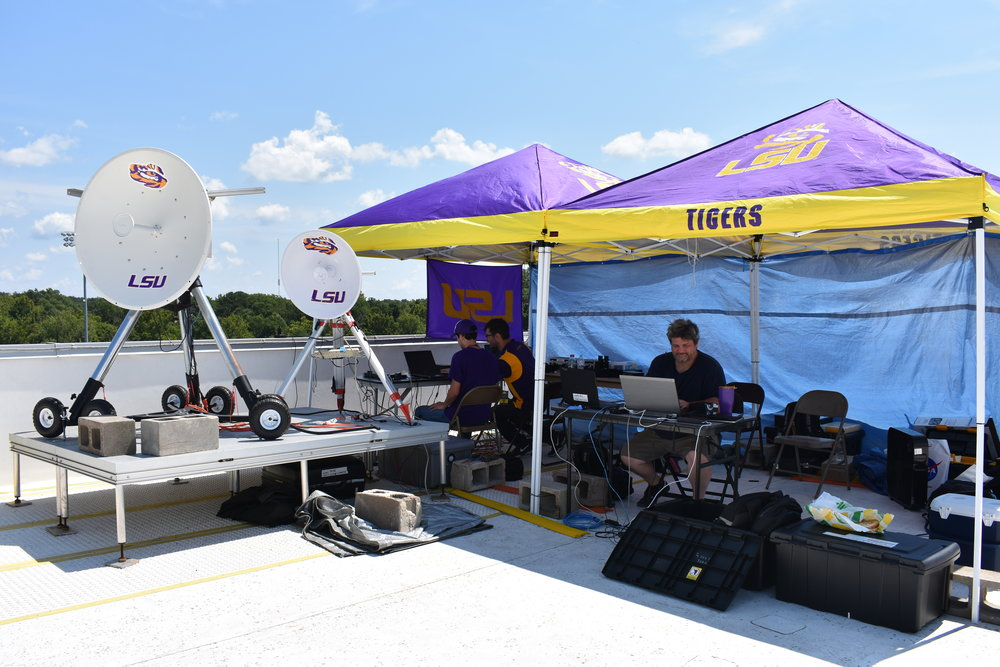 Ground station on the roof of Saluki Stadium with Doug Granger (right) and students Chris Shayer and Nicholas Pate (left).  The dishes (primary and backup) on the left will receive the video from the balloon.  The ground station is also responsible for tracking the balloon until the balloon is recovered. Credit: Nicki Button.