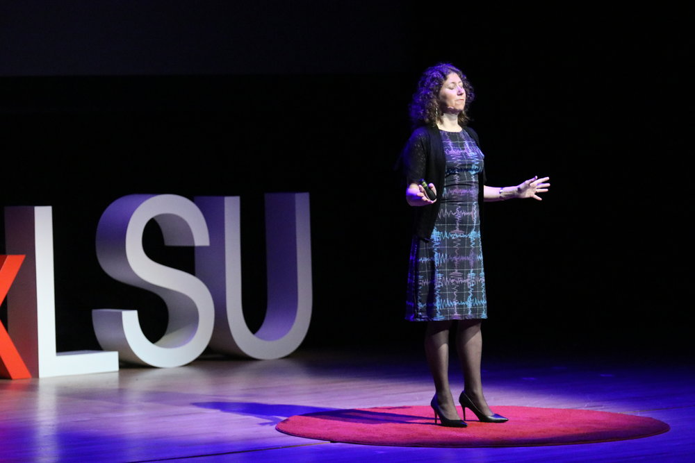 Photo of Gaby talking about gravitational waves at TEDxLSU. Credit: TEDxLSU.