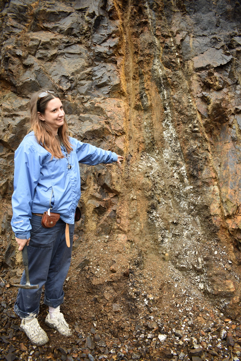 Dr. Amy Luther points to a fault damage zone with clay-like material on the left and veins of quartz. Photo Credit: Nicki Button