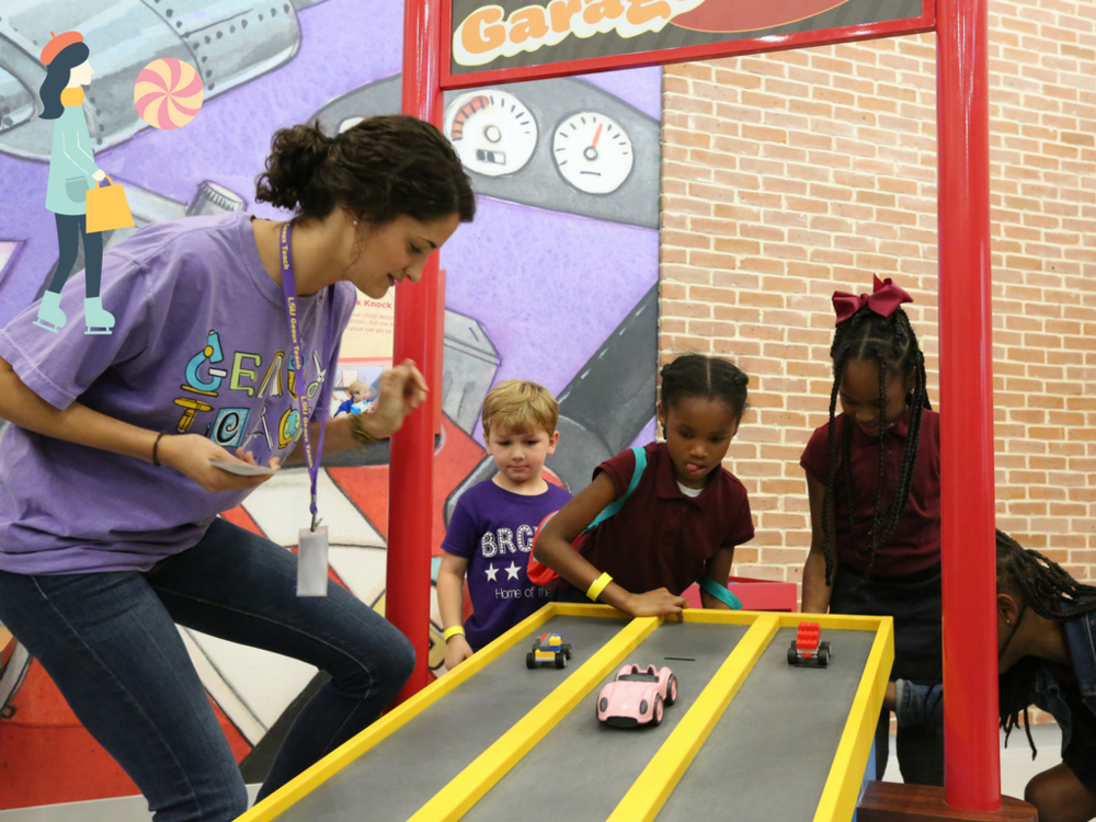 An LSU GeauxTeach student helps Knock Knock museum visitors test designed LEGO cars on the inclined ramp in the Go Go Garage.