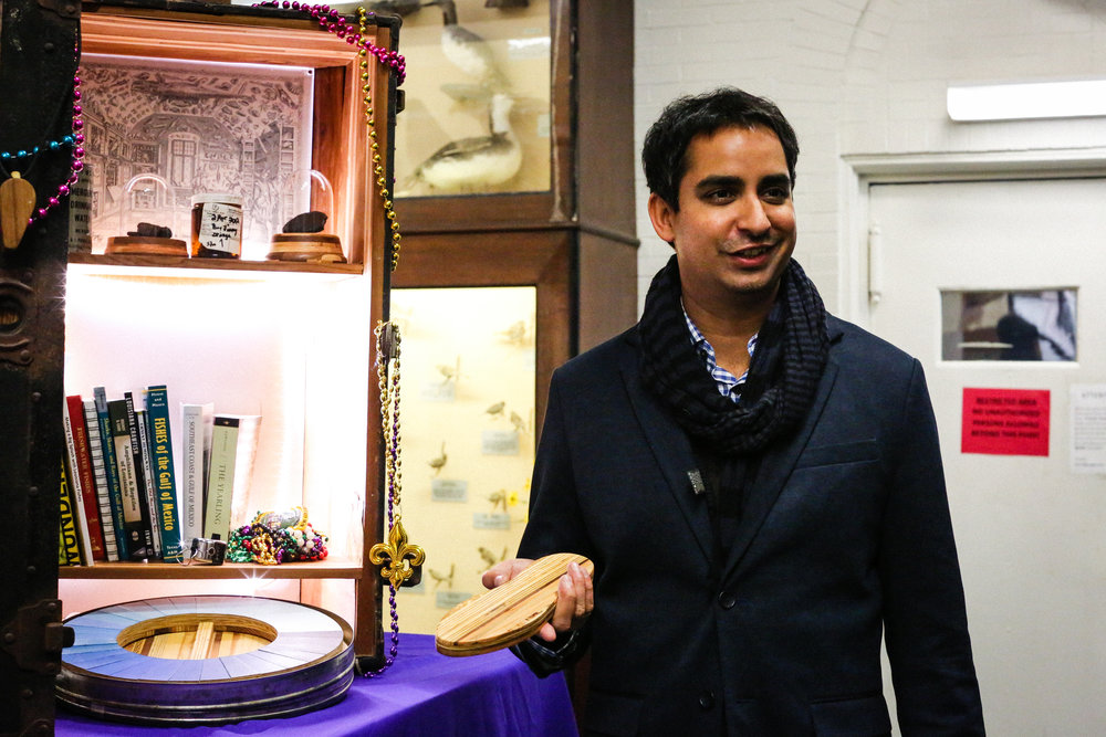 "Prosanta Chakrabarty introduces Crude Life to visitors at the LSU Museum of Natural Science. He holds a piece of wood fashioned from the wood of several prominent science and natural history museums around the country. Visitors can step on the piece to ""step into"" the halls of some of greatest museums in the country. Photo by Paige Jarreau."