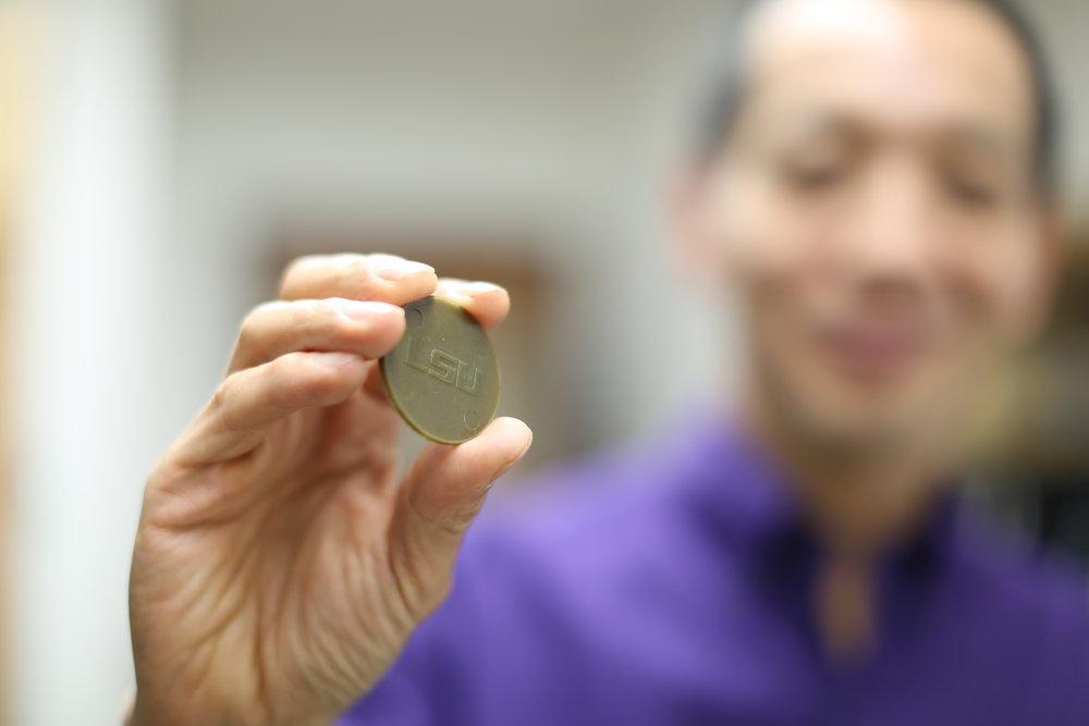 Dr. Kato has created biodegradable Mardi Gras medallions. Photo by Paige Jarreau.