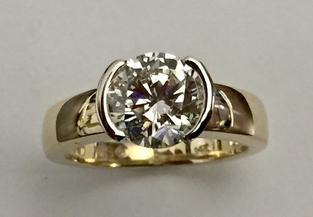 This diamond went from dated to contemporary in a half bezel two tone setting, now more wearable in a lower setting!