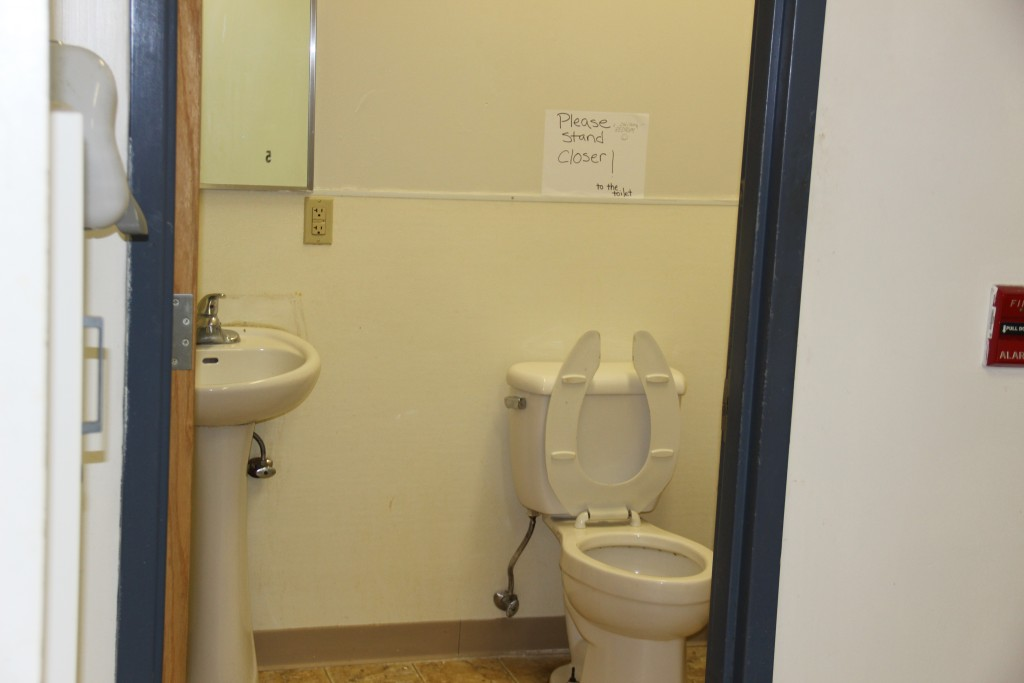 The single bathroom in the men's dorm area, which houses about 20 beds. A sign indicates for men to stand closer to the toilet to avoid messes that need to be cleaned by CHUM's small staff.