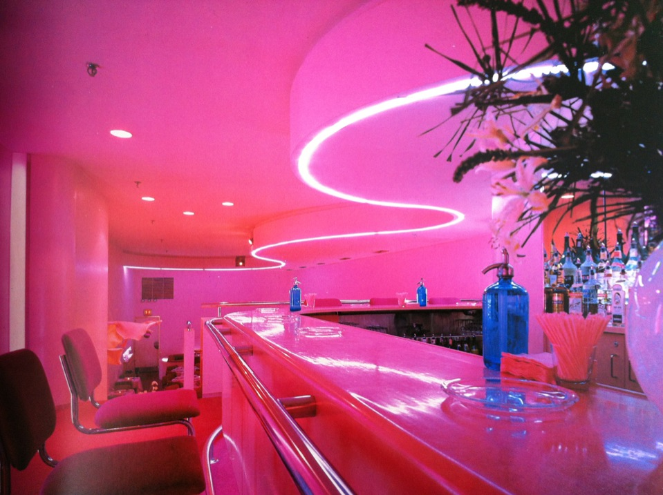 80sdeco :     undulating ceiling trimmed with pink neon, blue glass seltzer bottles, chrome and magenta fabric cantelivered bar chairs.