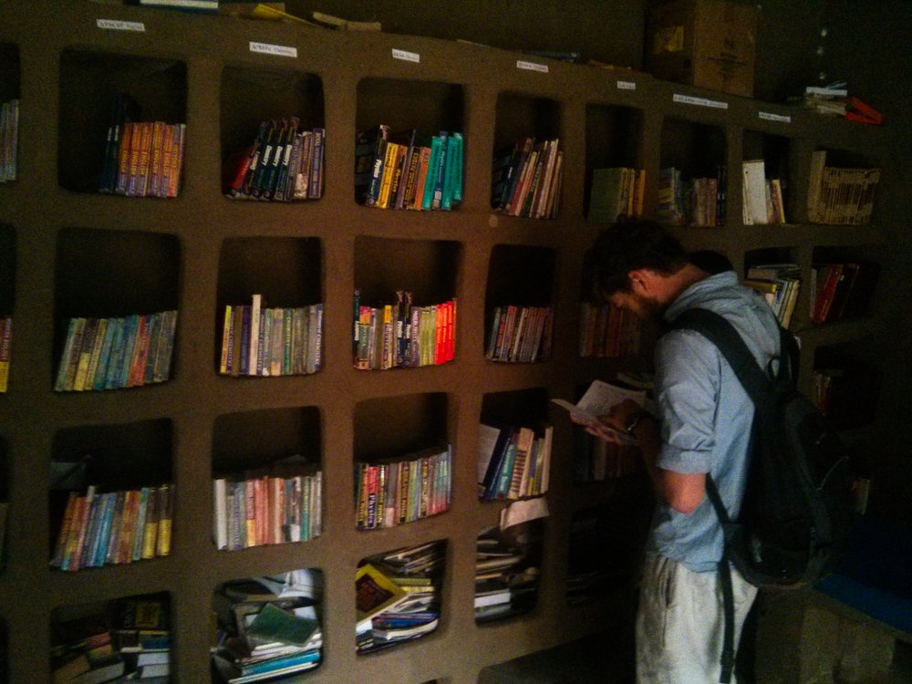 Perusing the mud shelves of the community library... (Photo Credit: Nick Colwill)