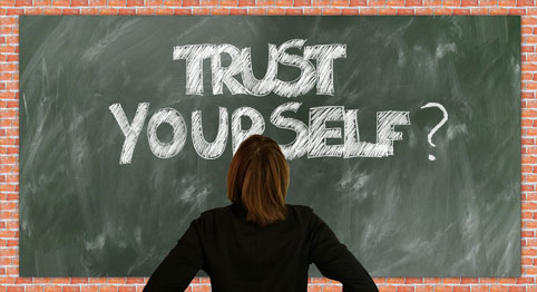 lady looking at chalkboard that says Trust Yourself?