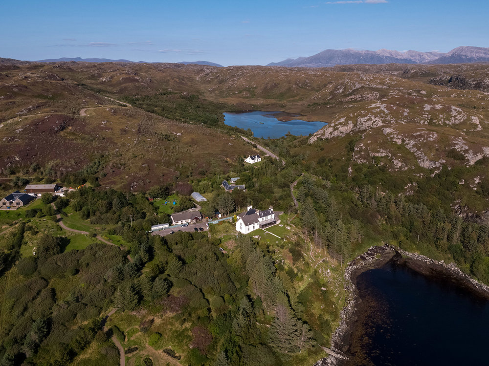 Eddrachilles Hotel - former manse is set proudly right above the bay. The small white building close to the loch is the former  church.