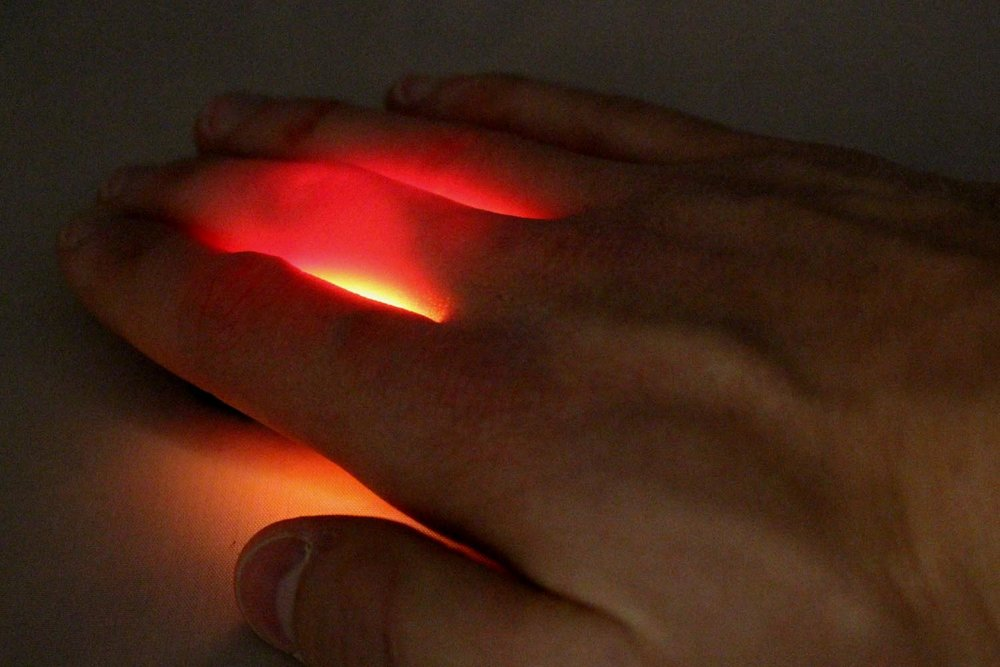 - Fingers placed over a white light source. Only red light can be seen because other parts of the visible spectrum are absorbed by the tissues which make up the hand.