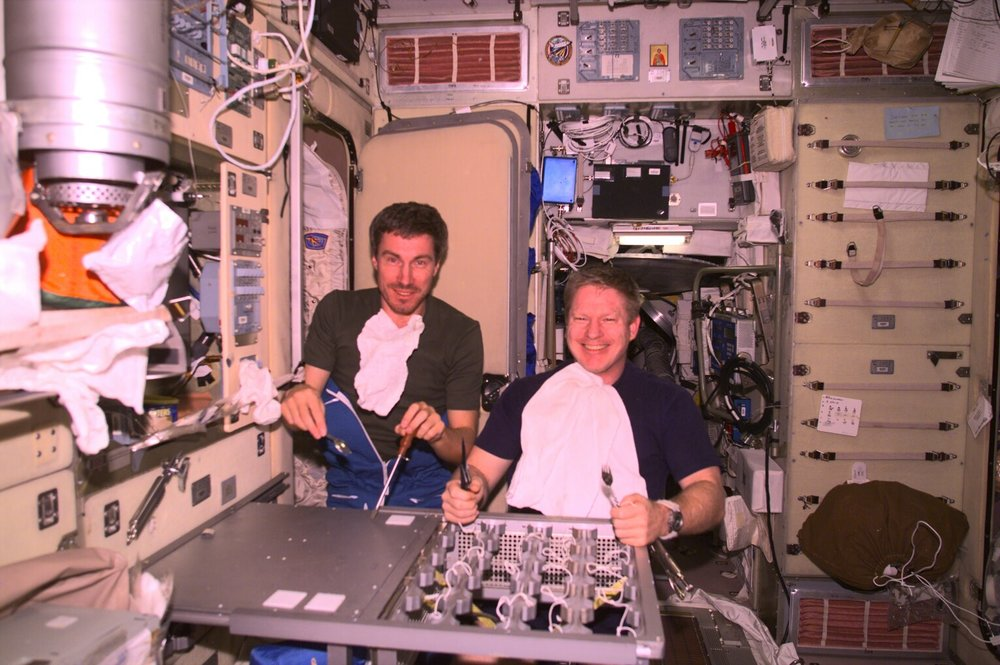 """Sergei Krikalev (left) and Bill Shepherd at their almost-finished table. """" Sergei's side has an aluminum panel cover screwed down,"""" says Shep. """"The right side does not have the top panel on yet. The ribs under the table surface visible on my side are part of the shipping brackets for the canisters that were originally in the large aluminum frame. Two of them were trimmed and joined to make up the body of the table. Photo Courtesy:Ginger Kerrick"""