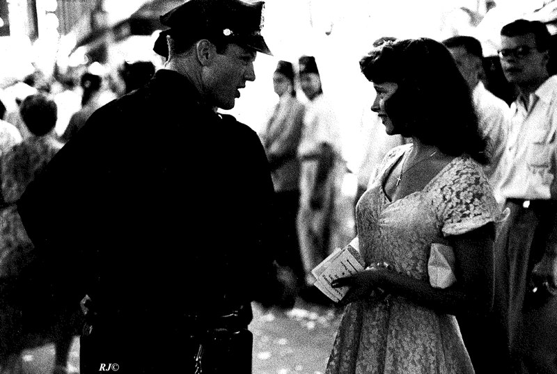 Shriners' parade/cop with girl, Times Square, 1952
