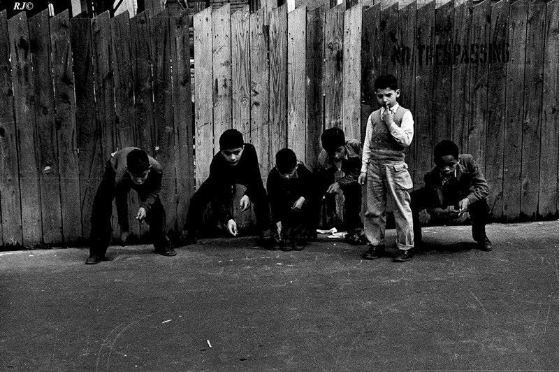 Boys playing against wood fence, Manhattan 1954
