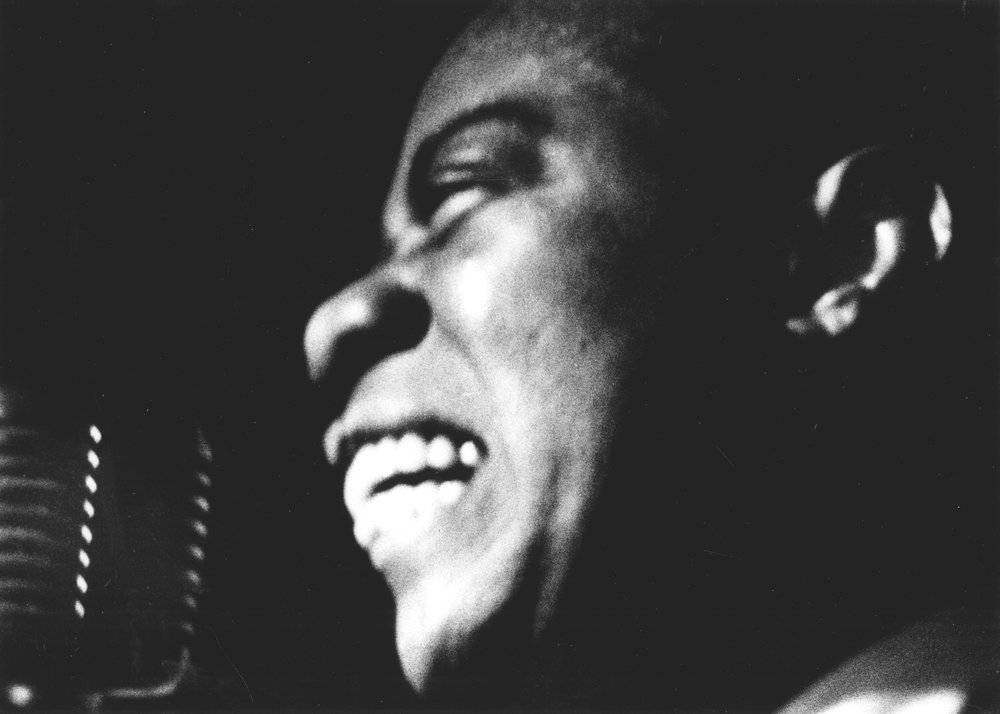 Smiling profile on stage, Basin Street East, 1954