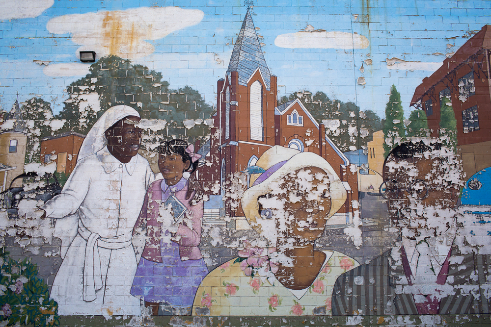 A mural of Durham's historic African-American Hayti Community at the Heritage Square shopping center is disintegrating. Older residents say Hayti was ruined in the 1960s and 1970s by urban renewal projects including the Durham Freeway, which cut off thriving black businesses from downtown. Others suggest that Hayti was already declining through unemployment and people leaving the neighborhood and that its demise was inevitable.