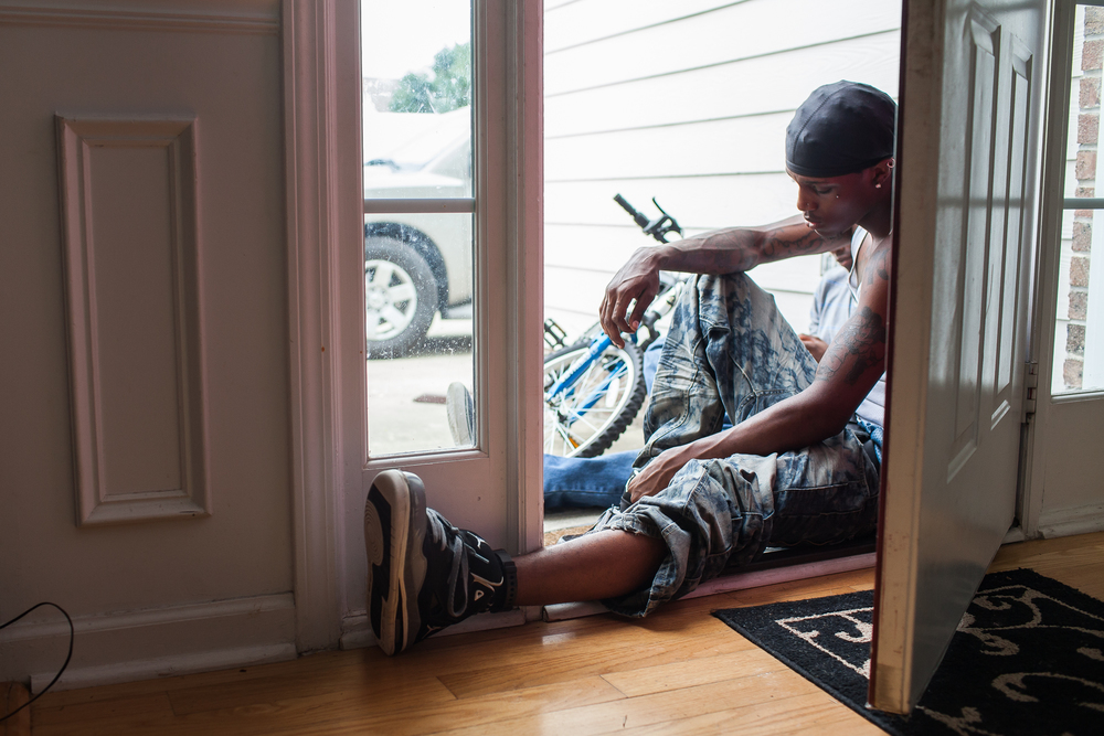 On house arrest for failing to pay his restitution, Rashard Johnson is afraid to set off his monitoring anklet, so he keeps one foot in the house while he smokes a cigarette in 2012. Rashard never knew his dad, and his mother did the best she could to make ends meet. He ran away from home, and at 16 he was arrested and charged as an adult for breaking into houses and possession of stolen goods. By 18, he was convicted of many nonviolent felonies. In 2012, when this image was taken, he had escaped gang life. He wanted to start over, and use his past to help other young black men. But Rashard's felonies follow him wherever he goes. These convictions make it difficult for ex-offenders to find a job, a place to live, to get an education and live a stable life. How will Rashard become more than his past if he is perpetually punished for his mistakes? North Carolina and New York are the only states that still prosecute 16-year olds as adults in felony cases. Durham recently passed an initiative banning the check box on employment applications that ask whether the applicant has been convicted of a crime or been incarcerated.