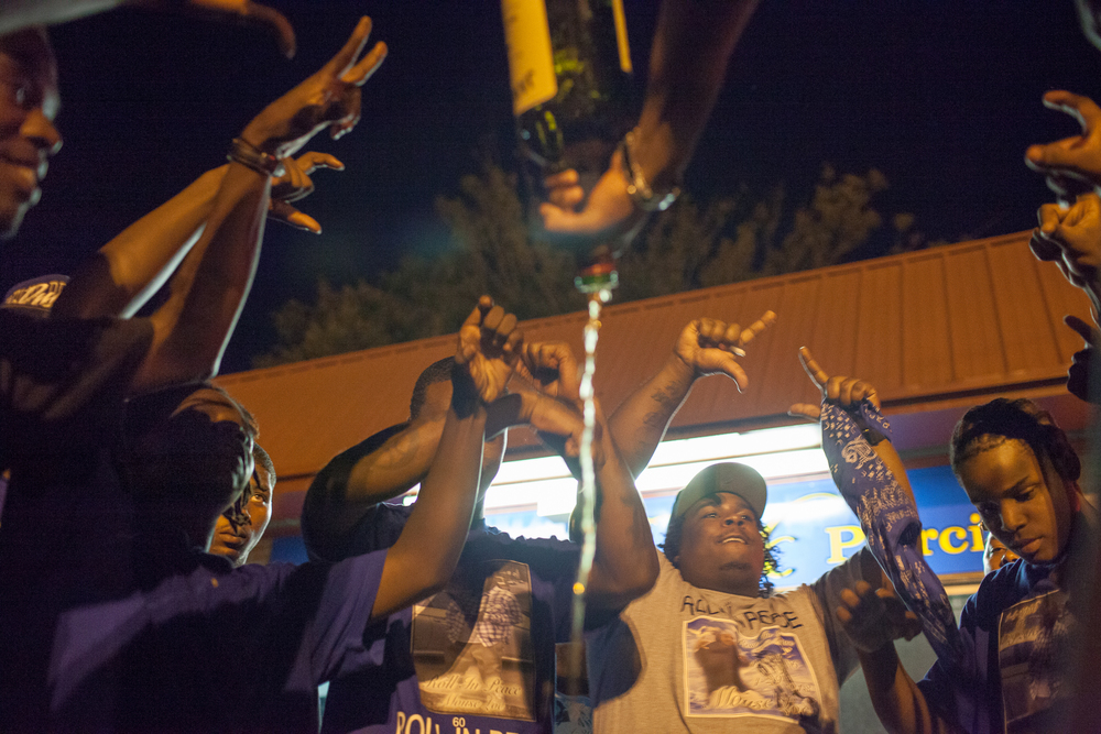 Young men who identify as Crips gather in a circle and spill liquor to mourn Maurice Streeter, who was shot and killed in April 2013. Neighborhood cliques and gangs offer young people a sense of purpose and family in neighborhoods torn apart by poverty and incarceration. The drug markets they often enforce are a substitute for a mainstream economy, which they are excluded from.