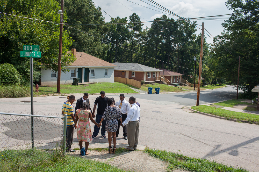 Congregants of Mount Gilead Baptist Church, led by Pastor Sanders Tate (far right), pray for peace at an East Durham intersection at the beginning of the 2013 school year.