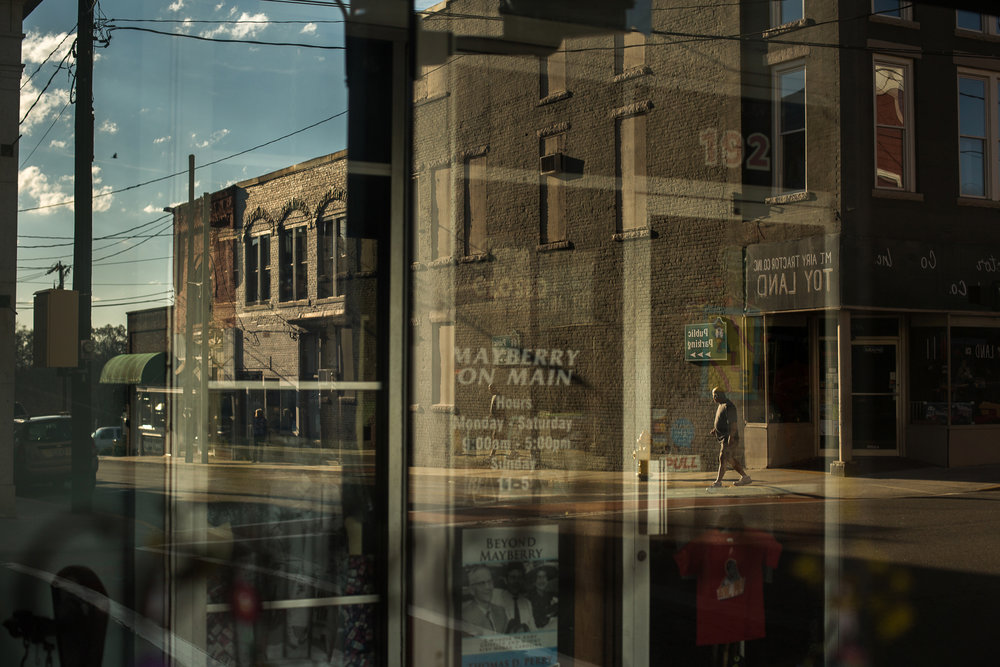 A street scene reflected in a storefront window in downtown Mount Airy, N.C., also known as Mayberry in the Andy Griffith show. Mount Airy is a cultural center in Surry County. For Education Week.