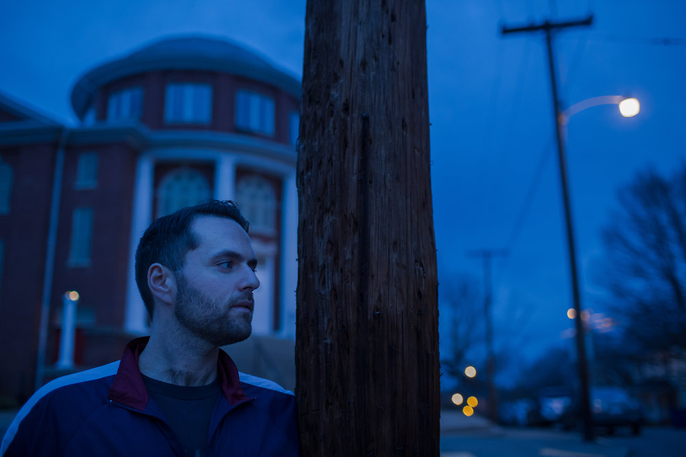 Colin Miller poses for a twilight portrait at Green Street Church in Winston-Salem, NC. The church houses The Twin City Harm Reduction Collective, a needle exchange and narcan distribution center for addicts, which he helped found after years of struggling with addiction.
