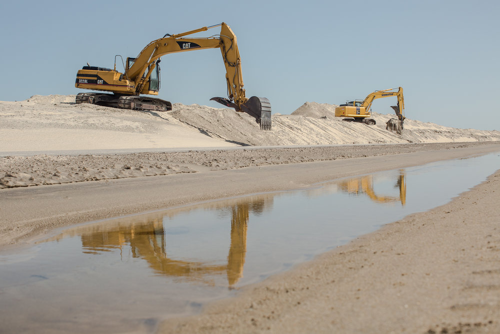 On Pea Island, bulldozers scrape sand off N.C. Highway 12 and shape it back into barrier dunes after Tropical Storm Jose breached them in September 2017. Hurricanes and other violent storms wash sand across these thin barrier islands, and they grow and migrate toward the mainland. But miles of man-made dunes that protect expensive beach homes and N.C. Highway 12 — the sole asphalt artery that threads the island villages — prevent this overwash and the island-building process. Instead the islands are locked in place, and angrier, more frequent storms inflamed by warming ocean temperatures are rapidly eroding them.