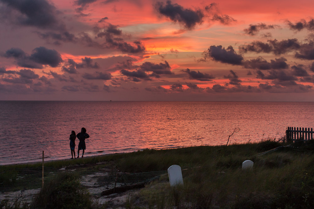 A couple takes in the sunset across the Pamlico Sound by the cemetery.