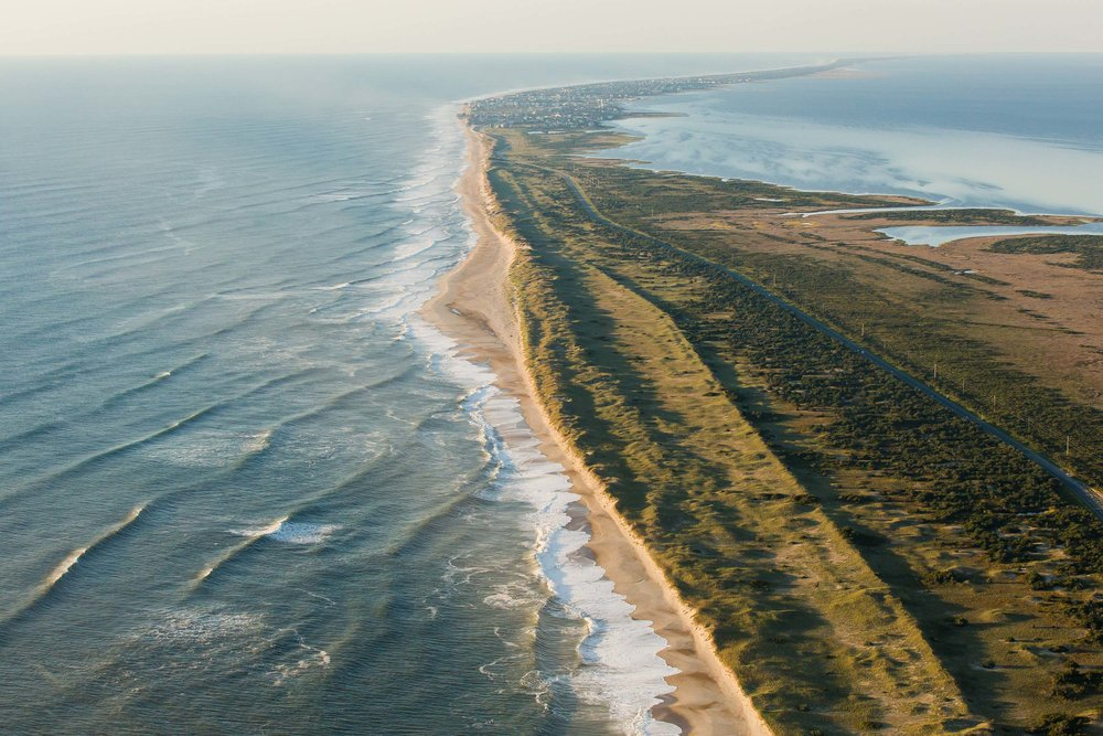 An aerial view of the Atlantic barrier dune ridges and NC Highway 12 on Pea Island, looking south towards the villages of Rodanthe, Waves and Salvo. Outer Banks residents live in constant tension with the edge of the sea.