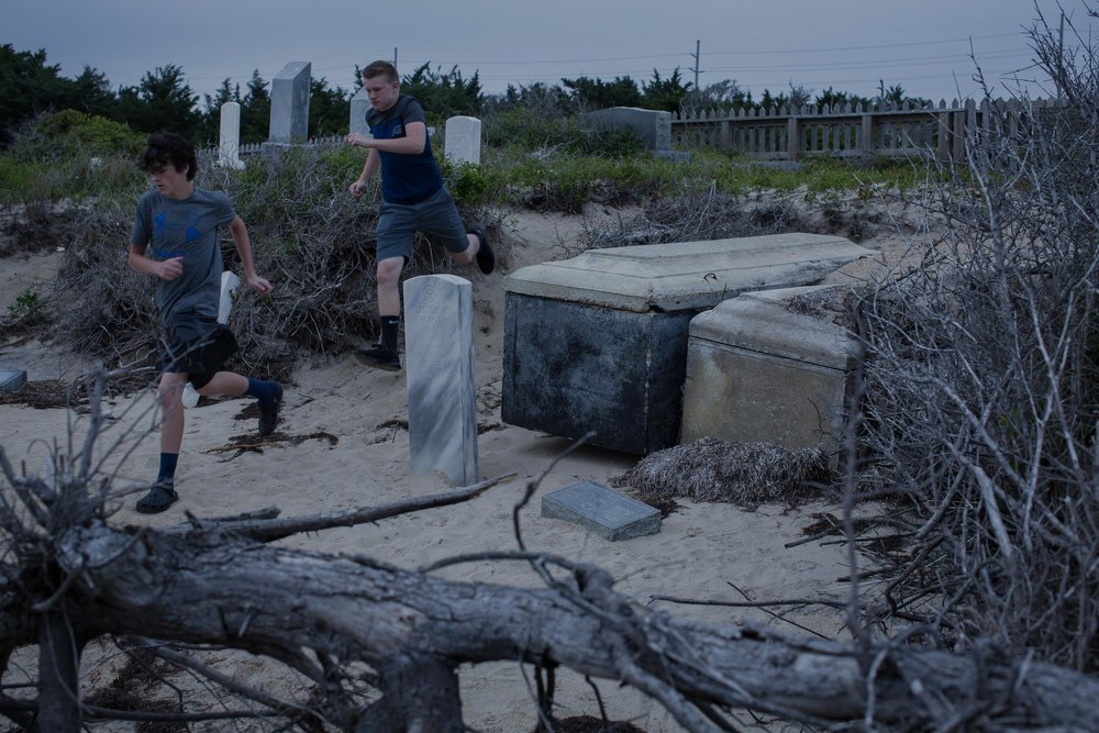 Tourists run past the graves of Little Pharaoh Payne, a WWII veteran, and his wife, Hilda, which have been exhumed by storm surge. Threatened by sea level rise, the cemetery is also vulnerable to erosion caused by foot traffic, which wears away the sand banks. Locals get irritated when tourists don't respect the resting place of their ancestors.