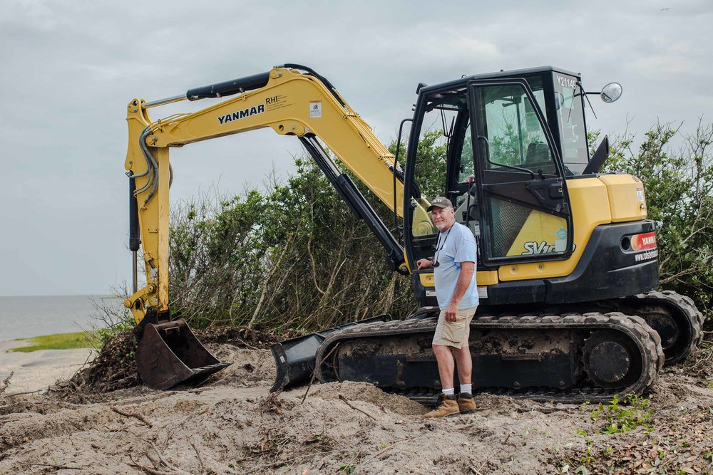 "David ""Cowboy"" Ambrose poses with his backhoe. His marine construction company is building a bulkhead that will slow erosion between the sound and the Salvo Community Cemetery. Decades ago, he fell in love with the Outer Banks and never left. ""People call me cowboy because wherever I take my boots off is my home,"" he says. May 2018."