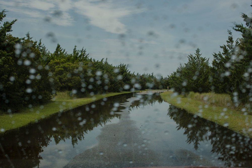 The entrance to the Salvo Community Cemetery. The spongey land stays flooded even after a summer thunderstorm. Sunny day flooding driven by wind and small storms is increasingly common on the Outer Banks.