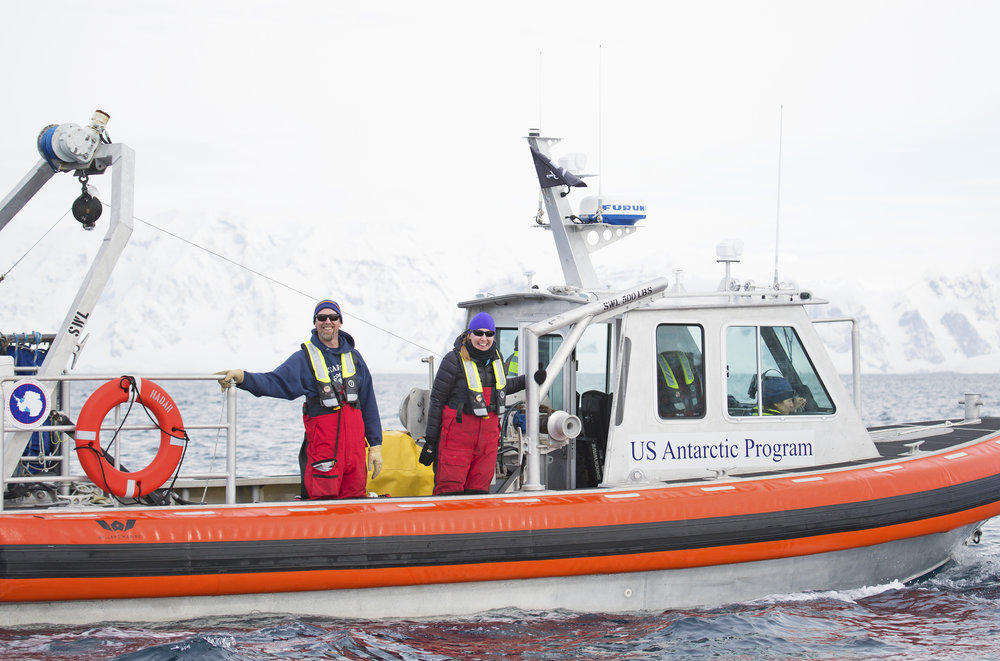 Eric Hutt and Amy Westman smile from the Hadar boat near Palmer Station.