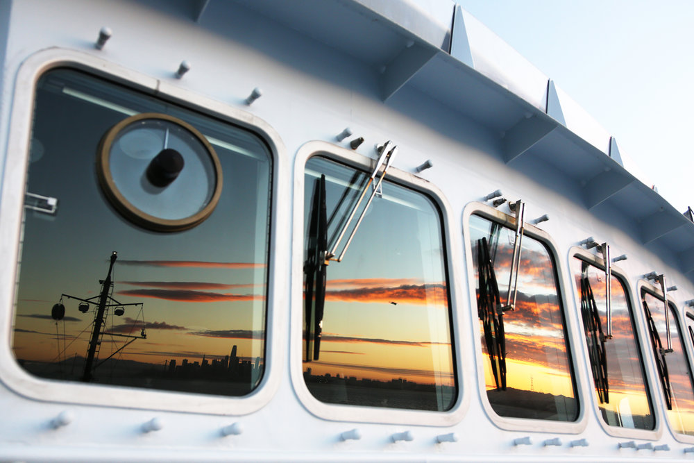 The bridge windows of R/V  Falkor  reflect sunset over San Francisco, California | October 2018