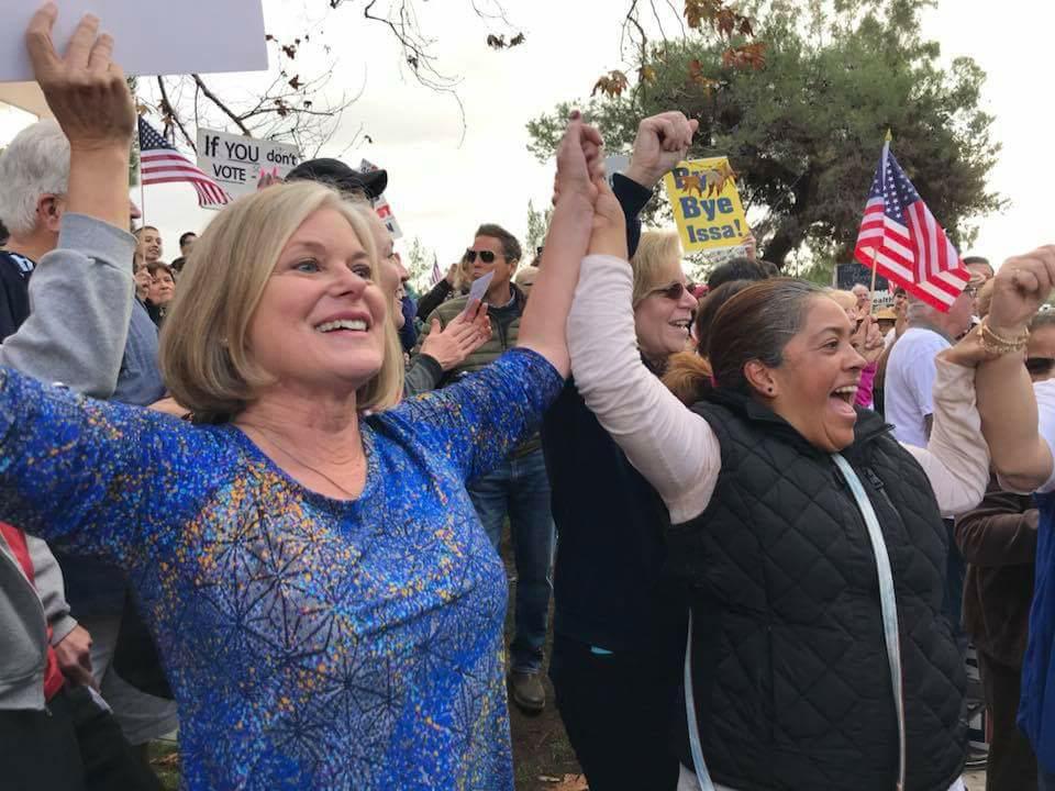 Demonstrators celebrate Congressman Darrell Issa's announcement that he was retiring. / Photo by Rachel Rott