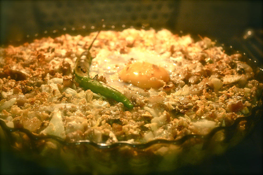 plopping an egg in the middle of the sisig