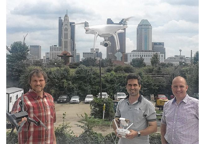 Steve Hane (center) of MetroAir Photo legally pilots his drone on the roof of the Murphy Co.'s building in Columbus, home of Autonomy Hub, while collaborators Loren Stone of the Tesla Foundation (left) and Dave Agler of Double I Media look on.