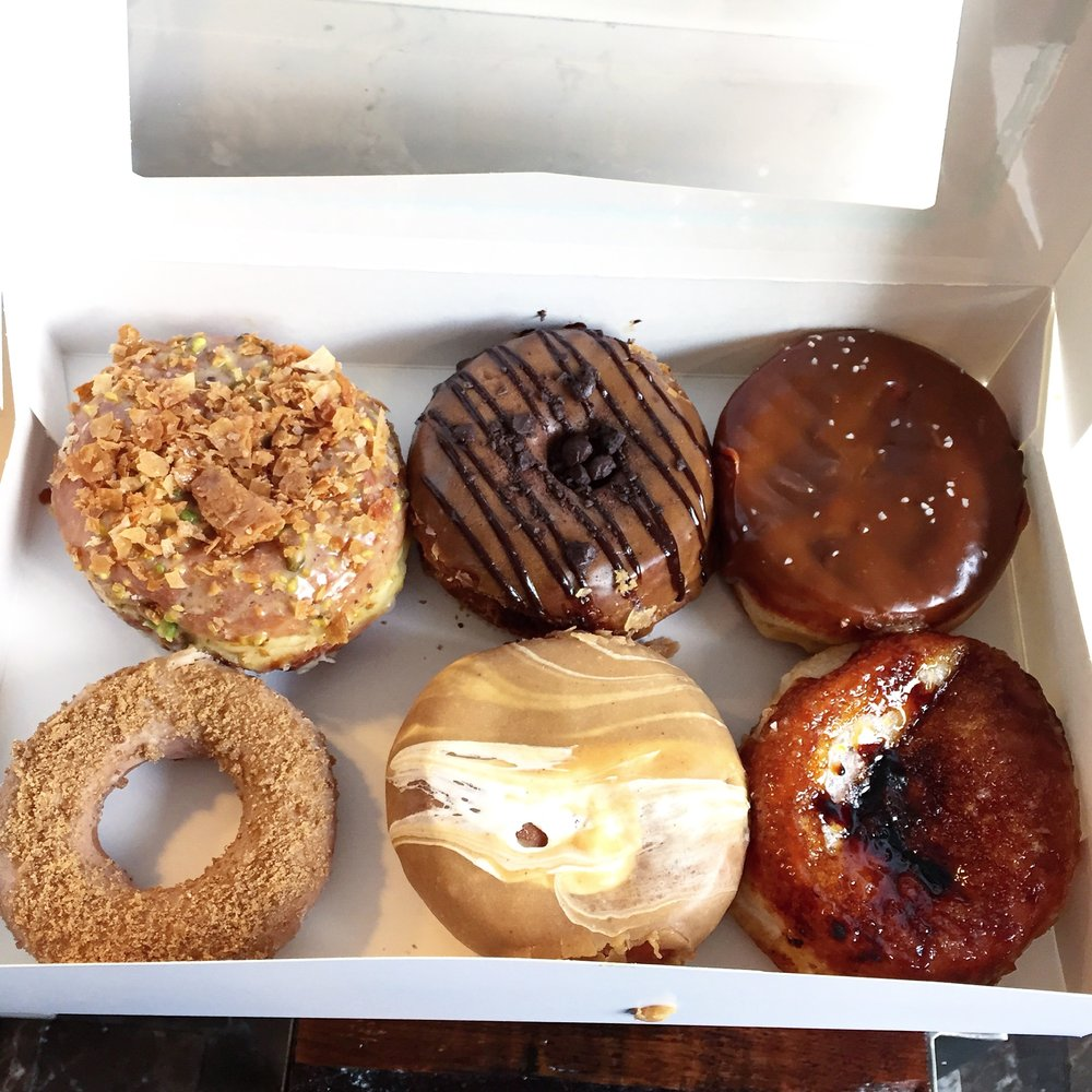 Left to right, top to bottom: Baklava, Dark Chocolate Ganache, Salted Dulce de Leche, Brown Butter, Fluffernutter, Creme Brulee from District Doughnuts