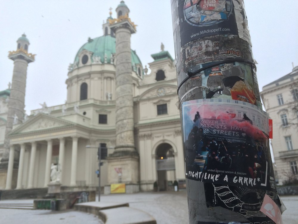 Antifascist sticker in Karlsplatz, the structure in the background is St. Charle's church.