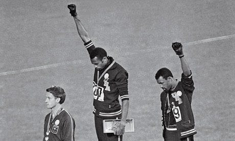 John Carlos and Tommy Smith raise black fists in protest during the 1968 Olympics. (Image: The Guardian)