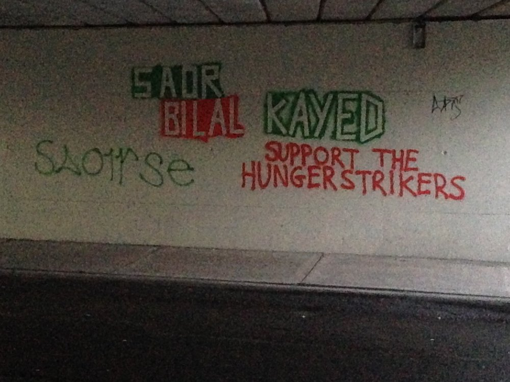 "Green and orange spray painted messages seen underneath the Dyke Road bridge at the beginning of 2017. ""  Saoirse""   meaning ""Freedom"" and ""  Saor Bilal Kayed  , SUPPORT THE HUNGERSTRIKERS"", ""  saor""   meaning ""free""."
