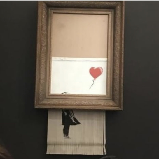 Banksy's famous  Girl with Balloon  is stopped halfway through a built-in shredder in the bottom of the frame.