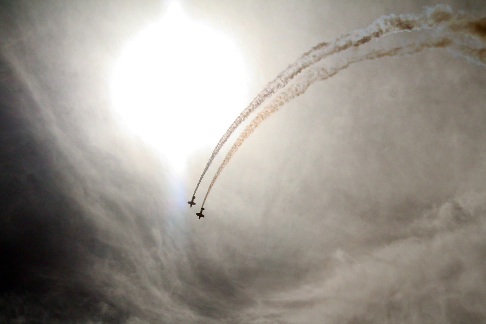 A pair of pilots fly below cirrus clouds lit by a midday sun over Pittsburgh International Airport.