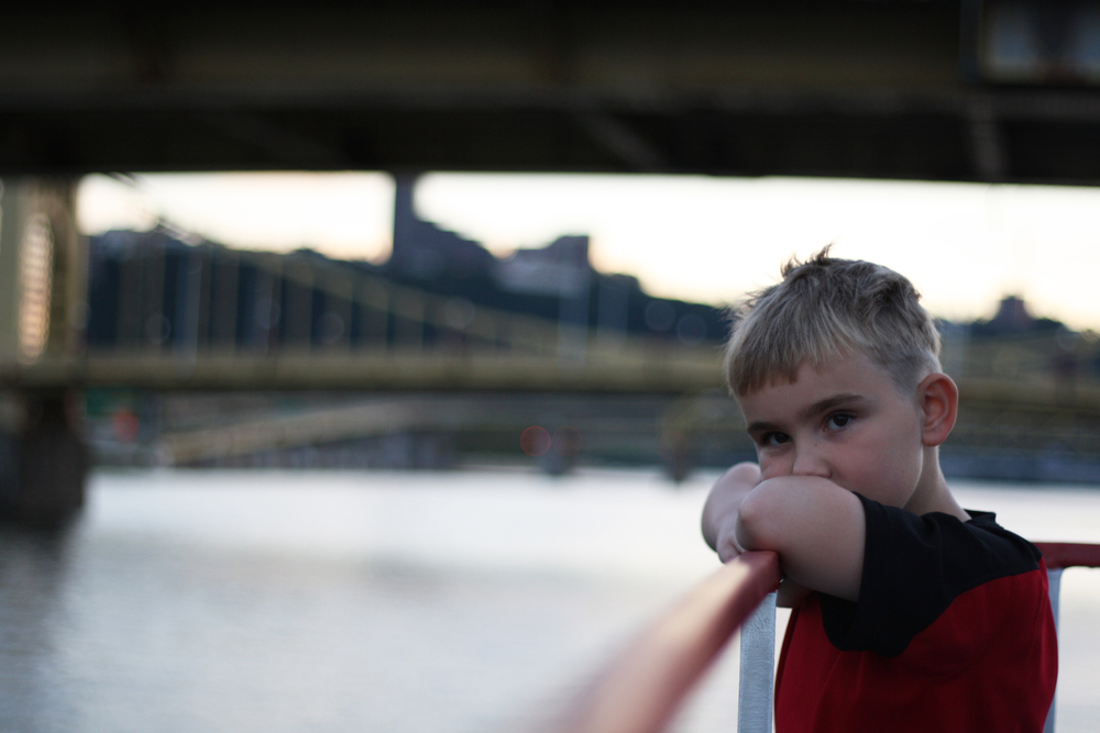 A boy leans on the railing of a boat as it passes beneath the Andy Warhol Bridge on the Allegheny River in Pittsburgh.