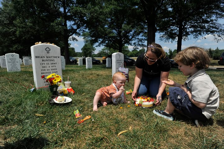 Nicki Bunting sits with her children, Connor, 2, and Cooper, 7 months, at the grave of her husband and their father, Captain Brian Bunting.  Photo credit:   Justin Merriman