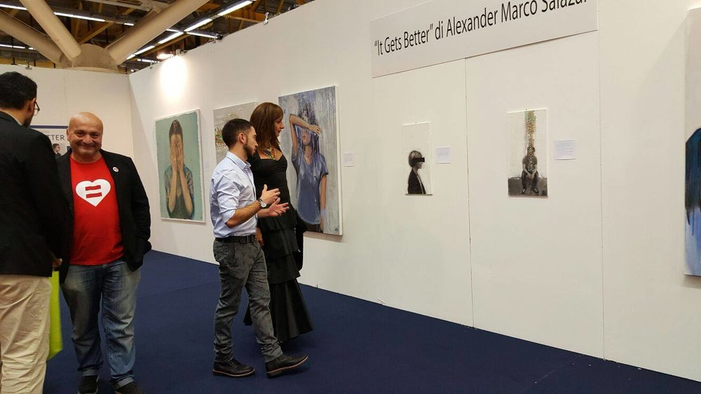 "Here, Alexander discusses his pieces with Vladimir Luxuria, the first transgender member of the European Parliament, at his latest  exhibition in Bologna: ""It Gets Better"", a series of paintings that analysed the stories of struggle, acceptance, and perseverance of the LGBT community in Italy."