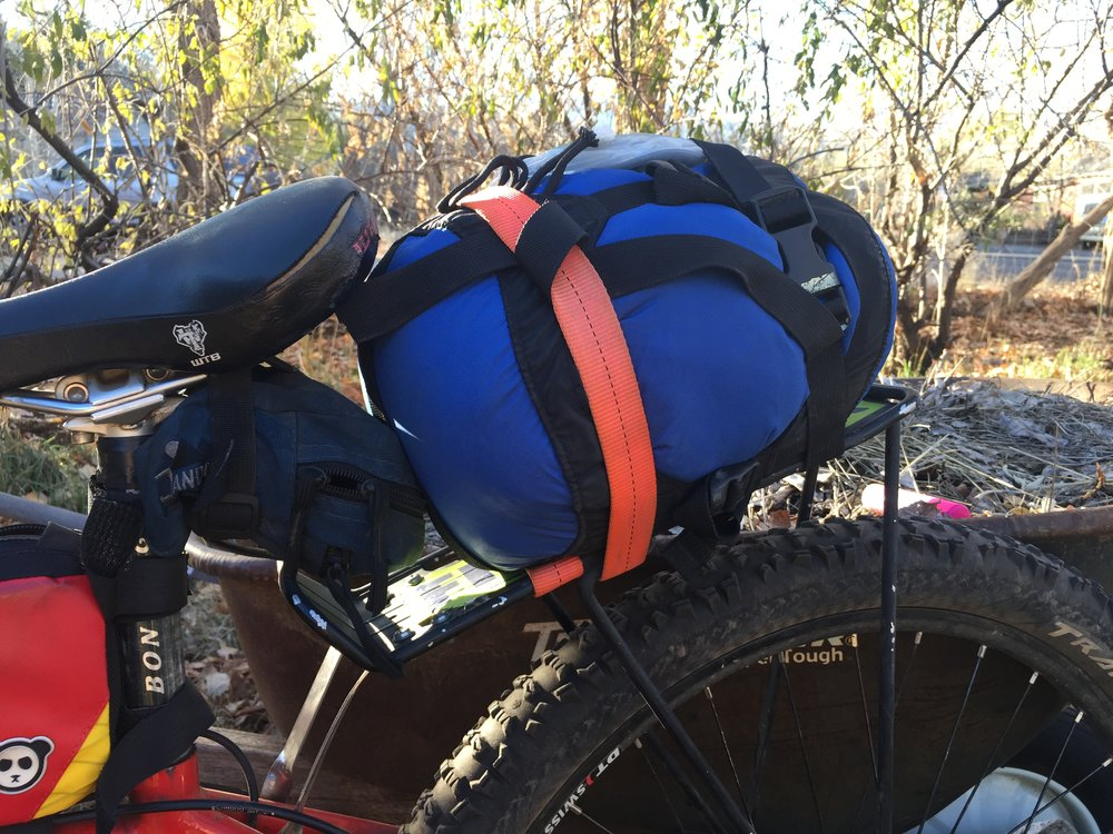 An up close of the rear set up. Sleeping Bag strapped directly to the rear rack with Luci on top. My ancient Jand tool bag under the seat. This poor tool bag has sort of lost the bounce in its bungy. I will likely replace this combo with a Rogue Panda Picket Post seat bag in the near future. This would eliminate the need for the rear rack altogether, save a bit of weight and eliminate the potential for a strap to come loose and get caught in the rear wheel.
