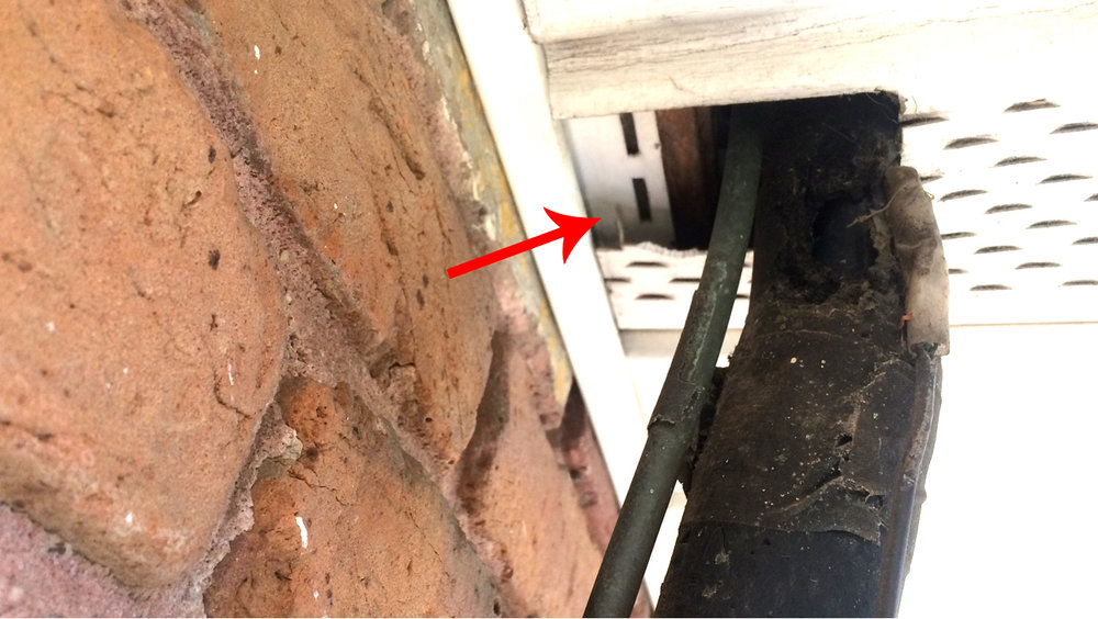 Access hole for pests at house eave where HVAC line enters